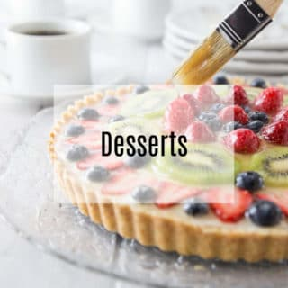 A photo of a French fruit tart with a pastry brush adding glaze.