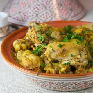 A photo of a tagine base with Moroccan saffron chicken inside.