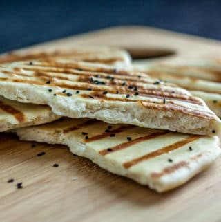 A photo of naan bread on a wooden cutting board.