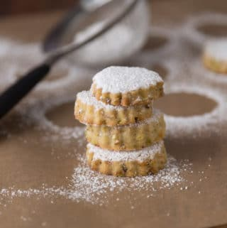 A photo of pistachio rosewater cookies with powdered sugar.