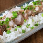 A photo of Thai pork loin on a bed of white rice with green onions.