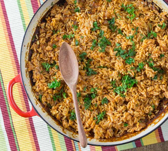 A photo of a large red pan with West African jollof rice and a wooden spoon.