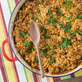 An overhead photo showing West African jollof rice in a red pan with a wooden spoon.