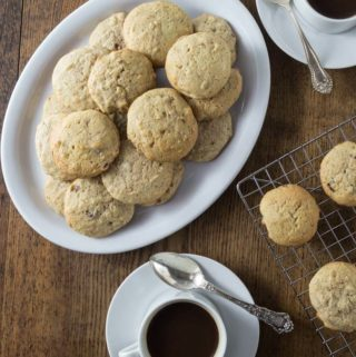 A photo of hermit cookies on a white plate with two cups of coffee.