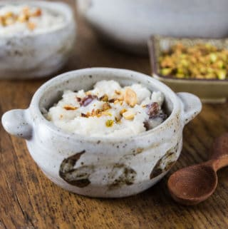 A photo of kheer and in bowl with nuts on top.