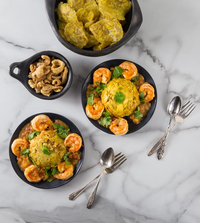 An overhead photo of plates with shrimp, mofongo along with tostones and plantain chips.