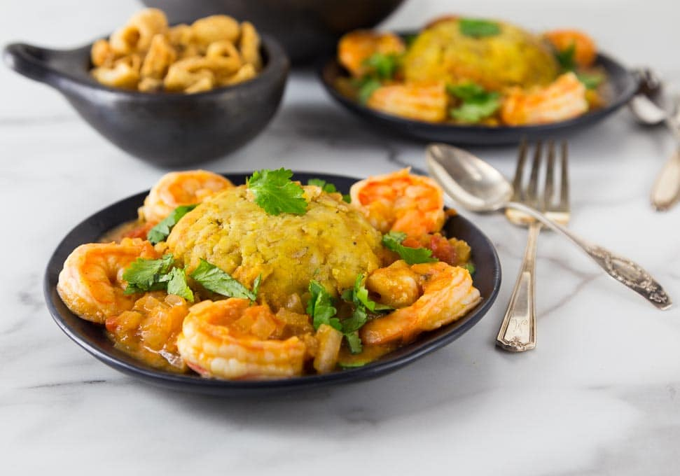 A photo of mofongo on a black plate with shrimp and sauce.