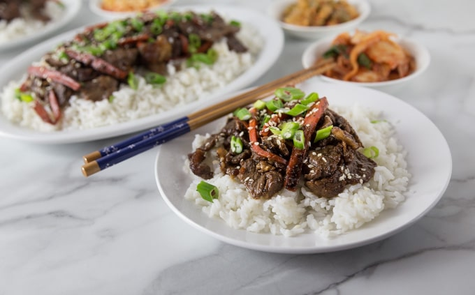 A white plate with rice, beef bulgogi and chop sticks.