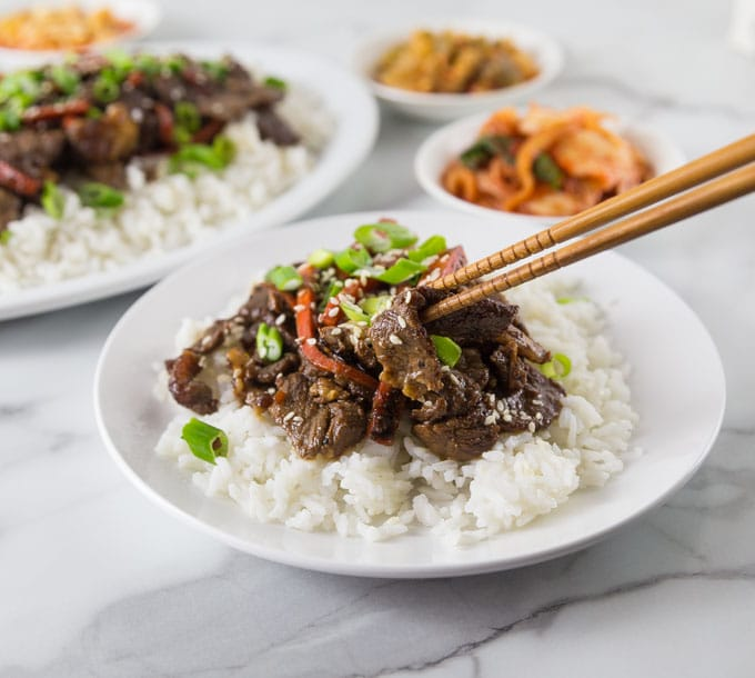 A photo of a white plate with rice and beef bulgogi and chop sticks picking up a piece of beef.