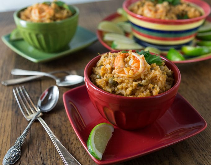 A red bowl with shrimp asopao and a lime wedge with silverware.